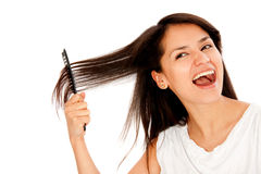 Woman combing her hair Stock Images