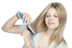Woman combing her hair Royalty Free Stock Image
