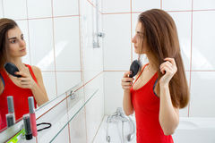 Woman combing her hair in the bathroom Stock Image