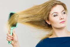 Woman brushing her long hair with brush Stock Image