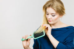 Woman brushing her long hair with brush. Woman combing her hair with brush. Young female with beautiful natural blond straight long hairs, studio shot on grey Royalty Free Stock Photography