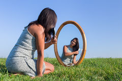 Woman combing her hair in mirror outside stock image