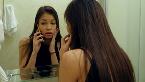 Woman combing her hair, preen and talking with her friend via smartphone in a hotel bathroom stock video footage