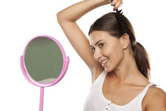 Woman combing her hair royalty free stock photos