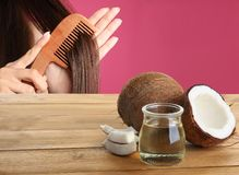 Woman combing her healthy hair and natural coconut oil on wooden table. Against pink background stock images