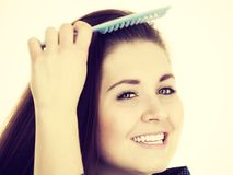 Woman brushing her long hair using comb Royalty Free Stock Photos