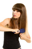 Woman combing her long brown hair with hairbrush Stock Photography