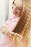 Woman combing her long hair in bathroom Stock Photography