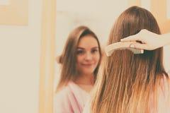 Woman combing her long hair in bathroom Stock Photos