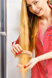 Woman combing her long hair in bathroom. Woman combing brushing her long smooth hair in bathroom with wooden comb. Girl taking care refreshing her hairstyle Royalty Free Stock Photo