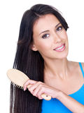 Woman combing her long hair with hairbrush. Smiling beautiful young woman combing her long brown hair with hairbrush - isolated stock photos