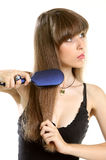 Woman combing her long hair with hairbrush. Smiling beautiful young woman combing her long brown hair with hairbrush - isolated Stock Image