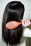 Woman combing her long hair with hairbrush Royalty Free Stock Image