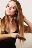Woman combing her long hair with wooden comb Stock Photos