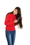 Woman combing her tangled hair. Stock Image