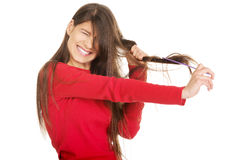 Woman combing her tangled hair. Royalty Free Stock Photography