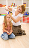 Woman combing little girls hair Stock Image