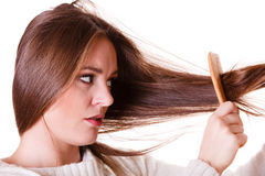 Woman combing and pulls hair. Dissatisfied woman combing with brush and pulls at her long hair. Feeling pain for nice look in daily activity Stock Photo