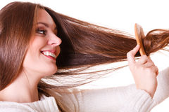 Woman combing and pulls hair. Dissatisfied woman combing with brush and pulls at her long hair. Feeling pain for nice look in daily activity Stock Photography