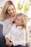 Woman combs hair of young girl Stock Photos