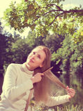 Woman combs long hair  on the river bank,with a retro effect Stock Images