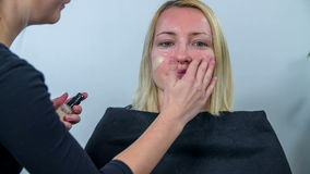 Woman comes to get her make up done stock video footage