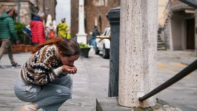 A woman comes to the water tower and sits down. Pours water into the hand stock video footage