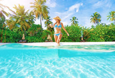 Woman comes into water on the beach Stock Photography