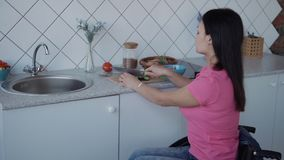 Woman in comfort wheelchair cooking healthy and green salad. Disabled female wearing in casual clothes sitting in comfort handicap indoor house with modern and stock footage