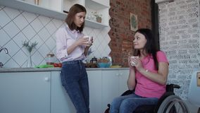 Woman in comfort wheelchair holding cup in hands and talking wit. Disabled female in casual wear sitting in special invalid chair or handicap inside bright house stock video