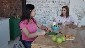 Woman in comfort wheelchair making salad and talking on kitchen. Disabled female in her casual clothes sitting in invalid chair or handicap indoor house with stock footage