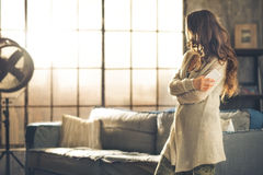 A woman in comfortable clothing in room. A brunette woman in comfortable clothing is standing in a loft living room, holding her phone, arms crossed, looking Stock Image