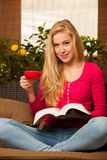 Woman comfortable sitting on sofa, reading book and drinking tea Stock Photography