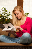 Woman comfortable sitting on sofa and using tablet computer. Stock Images
