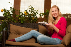 Woman comfortable sitting on sofa and using tablet computer. Stock Photography