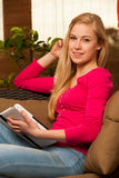 Woman comfortable sitting on sofa and using tablet computer. Royalty Free Stock Photography