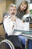 Woman Comforting Depressed Man In Wheelchair At Home Royalty Free Stock Image