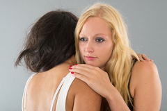 Woman comforting friend. Woman is comforting her sad friend isolated over gray background Royalty Free Stock Photo