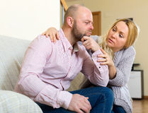 Woman comforting man. Man has problem, long-haired women comforting him in home Stock Photography