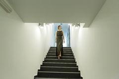 Woman coming down the stairs Stock Images