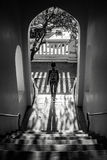 Woman coming down the stairs under a porch with beautiful sunlight and big shadow Royalty Free Stock Image