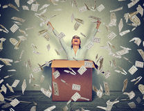 Woman coming out of box under money rain. Happy woman celebrates success coming out of box under money rain falling down dollar bills on gray wall background royalty free stock images