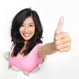 Woman coming out of a hole tearing and showing thumb up Stock Photo
