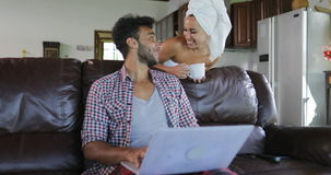 Woman Coming To Man Sitting On Coach Using Laptop Computer Browsing Online In Living Room, Young Couple In Morning. Woman Coming To Man Sitting On Coach Using stock video footage