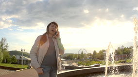 A woman communicates by phone at the fountain. A young woman in a white jacket stands on the side of a city fountain and sneezes while talking on the phone in stock video