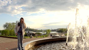 A woman communicates by phone at the fountain. A young woman in a white jacket stands on the side of a city fountain and sneezes while talking on the phone in stock footage