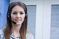 Woman communicating with headset phone. Call center  pretty  woman answering phone witrh headset Royalty Free Stock Photos