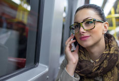 Woman commuter talking on cell phone Stock Photos