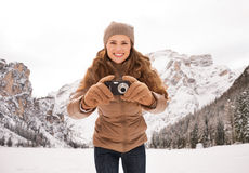 Woman with compact camera outdoors among snow-capped mountains Stock Images