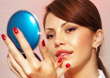 Woman with compact mirror l stock images
